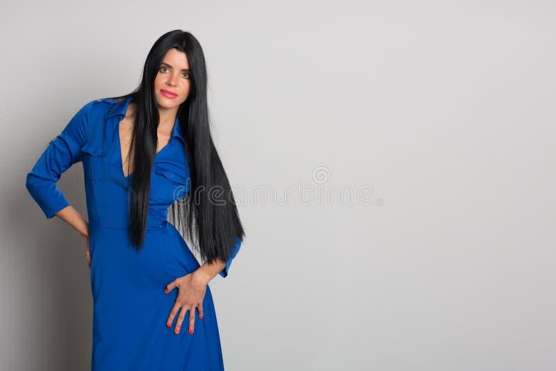 Mädchen mit dem schwarzen Haar in einem blauen Kleid lizenzfreie stockfotos