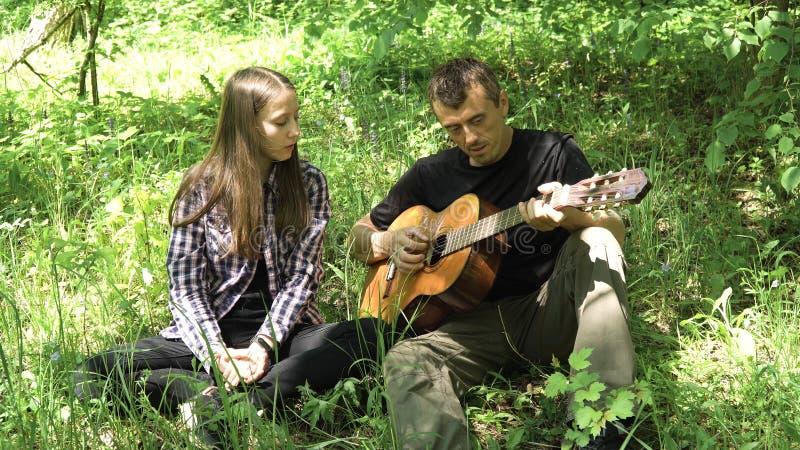Mädchen mit dem Vater, der die Gitarre spielt stockbilder