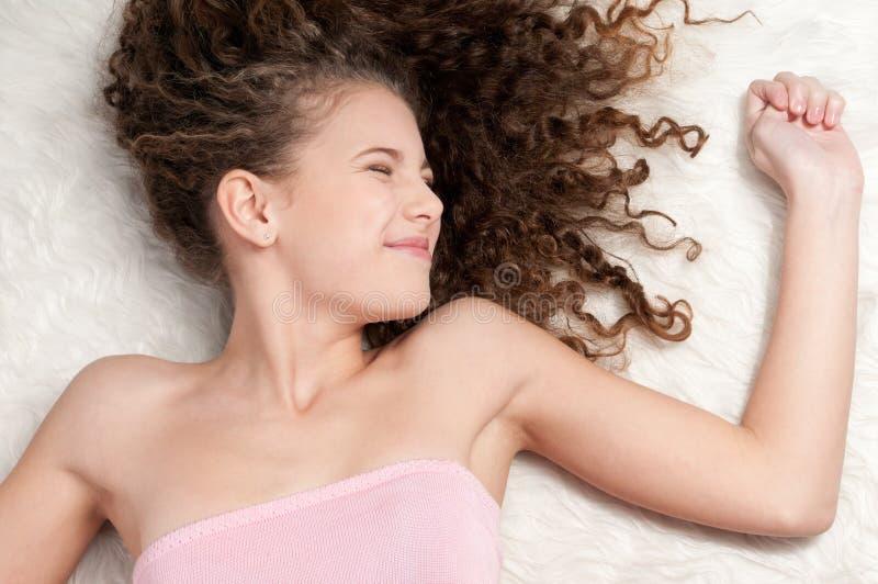 Mädchen mit dem vollkommenen lockigen Haar, das auf Pelzbett liegt lizenzfreie stockfotografie