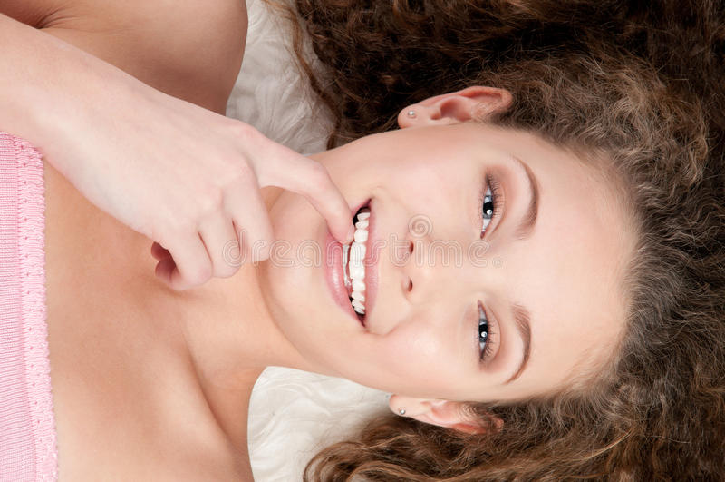 Mädchen mit dem vollkommenen lockigen Haar, das auf Pelzbett liegt lizenzfreie stockfotos