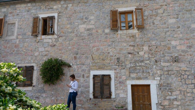 Mädchen mit dem weißen langen Hemd, das eine Mitteilung im intelligenten Telefon und Steinhaus mit Blumen in der Fassade sendet F stockbild