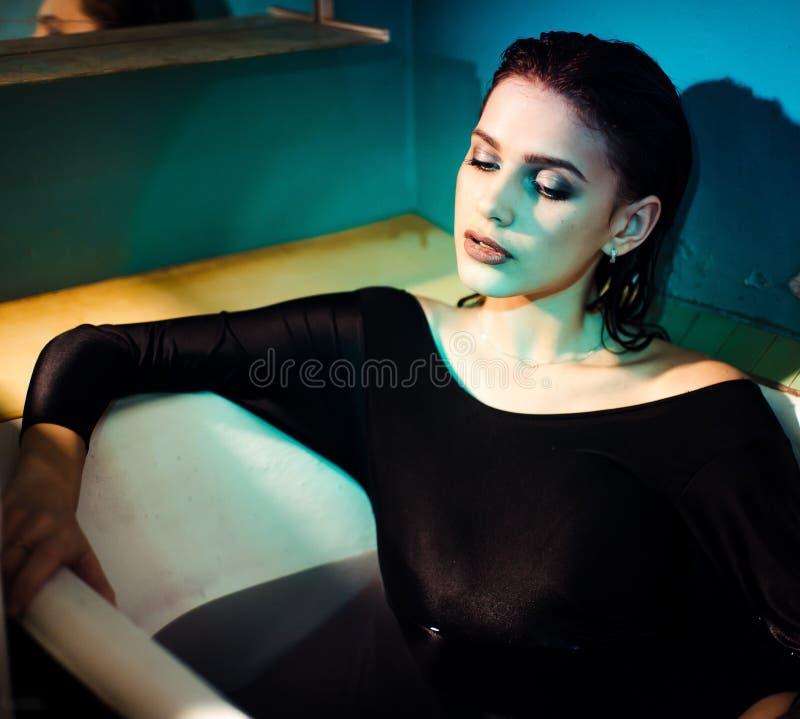 Mädchen mit den bloßen Schultern, die im Badezimmer mit farbigem purpurrotem Wasser liegen Art und Weisekonzept stockfotos