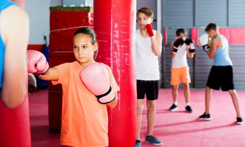Mädchen mit den Boxhandschuhen, die in verteidigter Position aufwerfen stockfoto