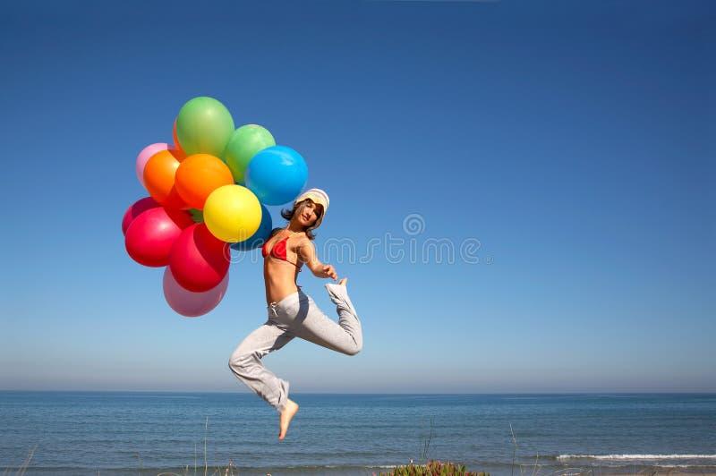 Mädchen mit den bunten Ballonen, die auf den Strand springen stockfotografie