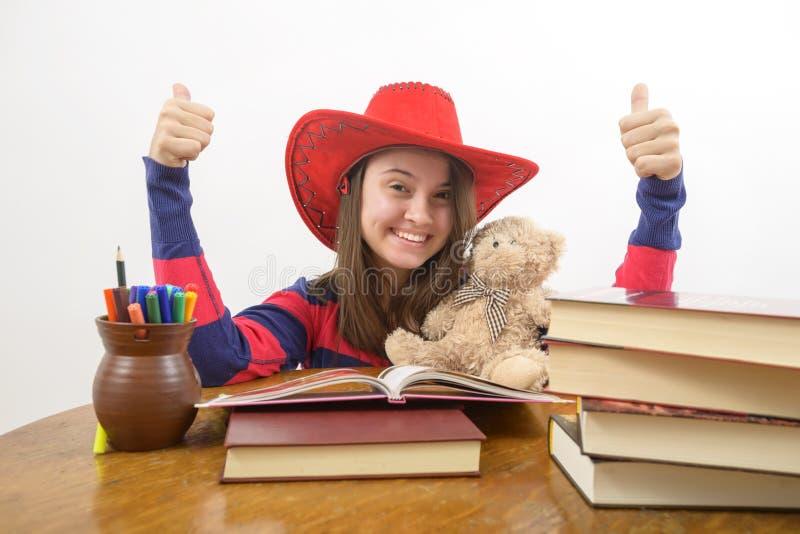 Mädchen mit den Daumen herauf das Zeichen, das am Tisch mit Stapel Büchern sitzt, stockbilder