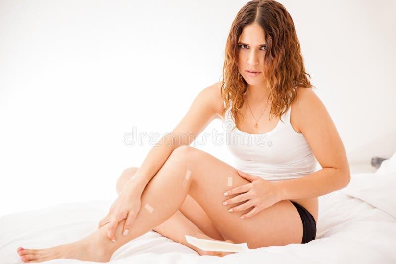 Mädchen mit den geschnittenen Beinen nachdem dem Rasieren lizenzfreie stockfotografie