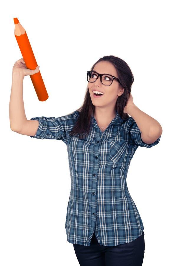 Mädchen mit den Gläsern, die riesigen orange Bleistift halten stockfoto
