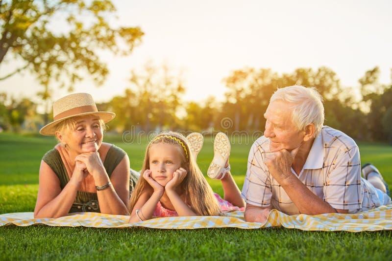 Mädchen mit den Großeltern, die draußen liegen lizenzfreie stockfotos