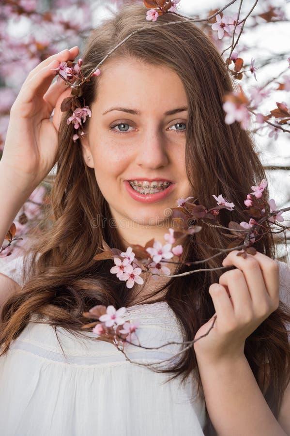 Mädchen mit den Klammern, die blühenden Baumast halten stockbild