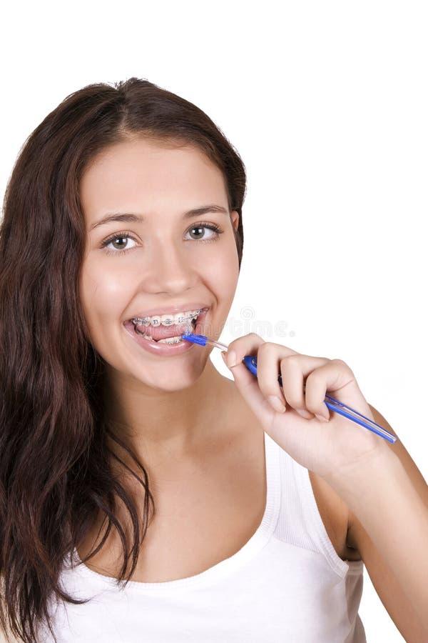 Mädchen mit den Klammern, die ihre Zähne putzen lizenzfreies stockbild
