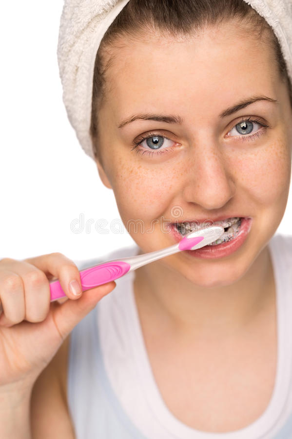 Mädchen mit den Klammern, welche die Zähne lokalisiert putzen lizenzfreie stockfotos