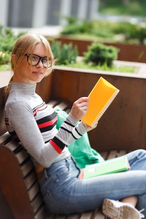 Mädchen mit den Notizbüchern, die auf Bank in der Straße sitzen lizenzfreies stockbild