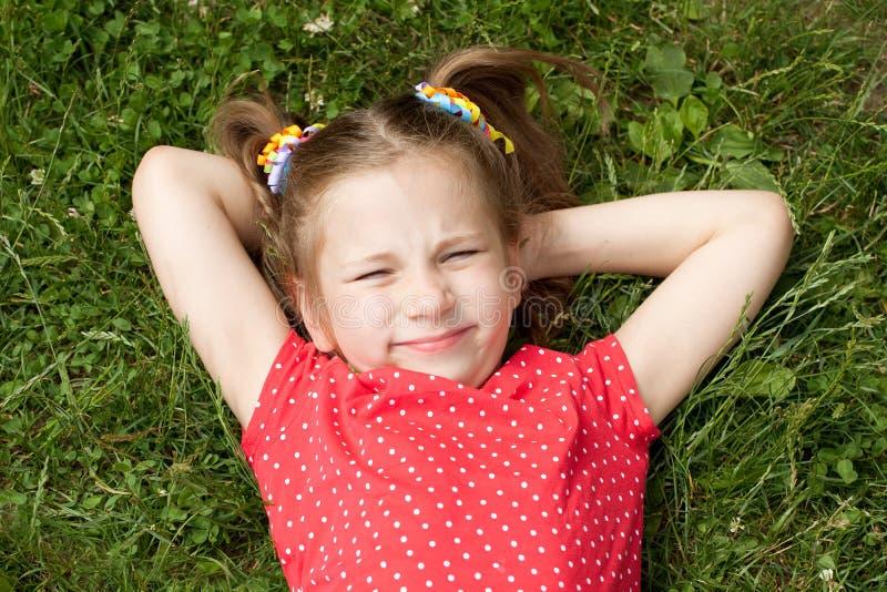Mädchen mit den Zöpfen, die auf Gras liegen lizenzfreies stockfoto