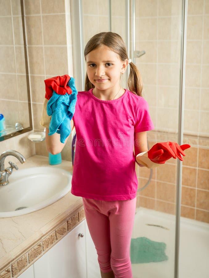 Mädchen mit den Zöpfen, die am Badezimmer beim Handeln des Säuberns aufwerfen stockfotos
