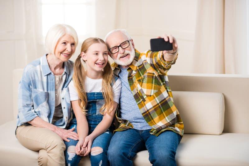 Mädchen mit der Großmutter und Großvater, die auf Sofa sitzen und selfie nehmen lizenzfreie stockbilder