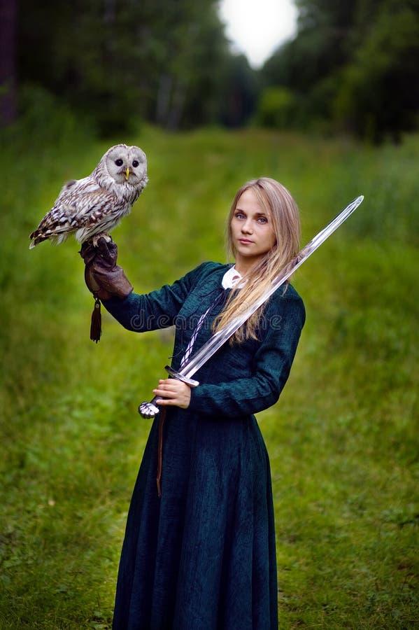 Mädchen mit der Klinge, die eine Eule auf ihrem Arm hält lizenzfreie stockbilder
