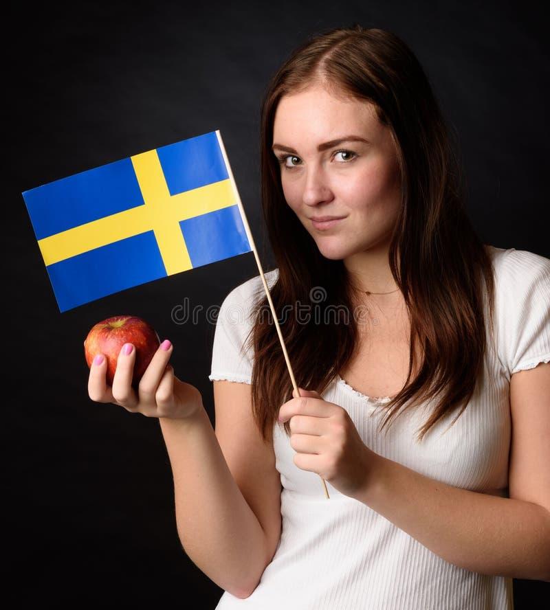 Mädchen mit der schwedischen Flagge, die einen Apfel u. ein x28 hält; Ingrid-marie& x29; lizenzfreies stockbild