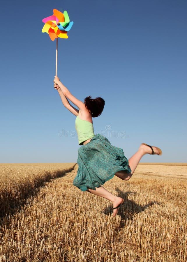 Mädchen mit der Windturbine, die am Weizenfeld springt lizenzfreie stockfotografie