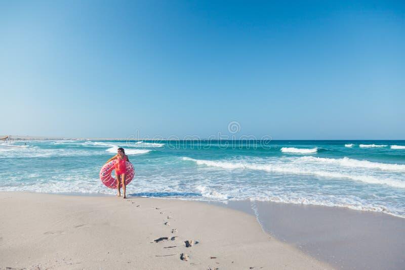 Mädchen mit Donut lilo auf dem Strand lizenzfreie stockfotos