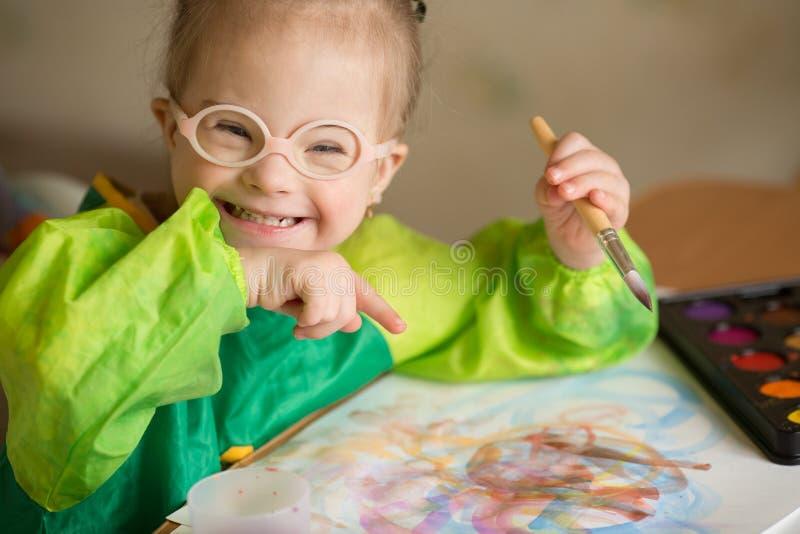 Mädchen mit Down-Syndrom zeichnet Farben lizenzfreie stockfotos