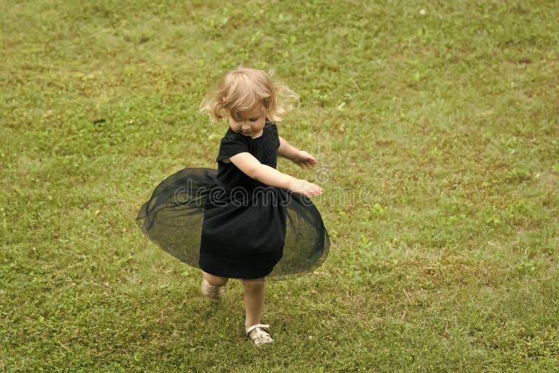 Mädchen mit Drehbeschleunigung des blonden Haares im schwarzen Kleid auf Gras lizenzfreie stockfotos