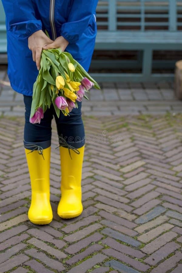 Mädchen mit einem Blumenstrauß von Frühlingstulpen im Rosa In einem blauen Regenmantel und in gelben Stiefeln auf der Straße in E stockfoto