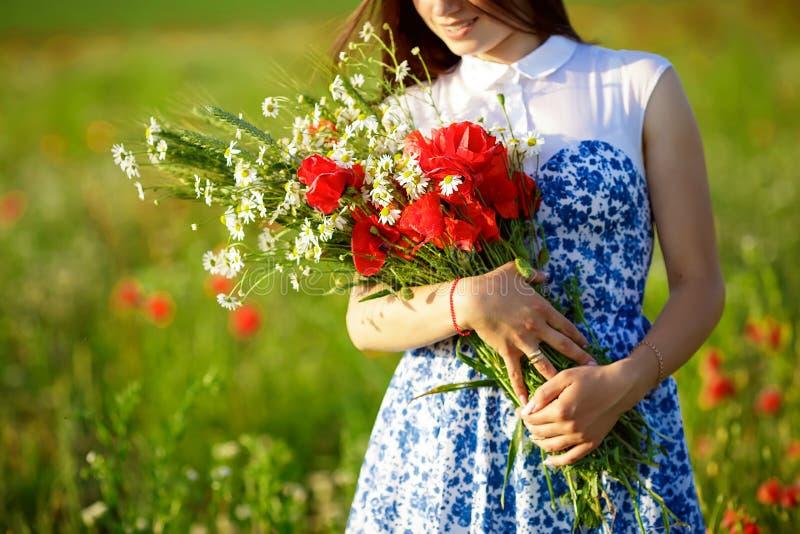 Mädchen mit einem Blumenstrauß von Mohnblumen Frau mit dem langen Haar im Kleidergriff-Blumenblumenstrauß auf dem Gebiet des Mohn stockbild