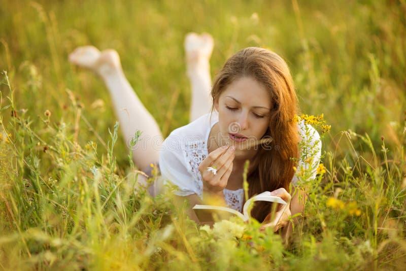 Mädchen mit einem Buch von Wildflowers stockfotos