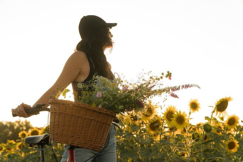 Mädchen mit einem Fahrrad und ein Korb von Blumen lizenzfreies stockfoto