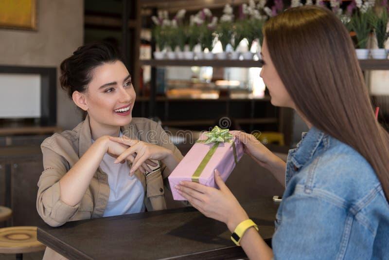 Mädchen mit einem Geschenk, das vor einem anderen Mädchen sitzt stockfotografie