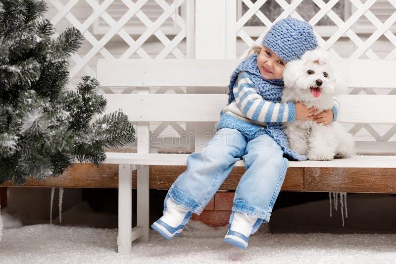 Mädchen mit einem Hund auf einer Bank außerhalb des Hauses lizenzfreies stockbild