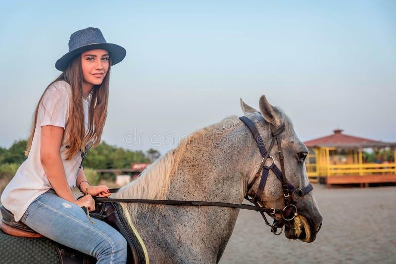 Mädchen mit einem Hut, der ein Pferd reitet stockbild