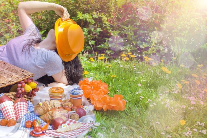 Mädchen mit einem Hut an einem Picknick, den Tag des Königs feiernd Orange Feiertag Joyfull-Wochenende Essen auf dem Gras Frühlin stockbilder