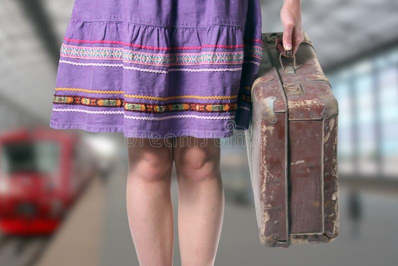Mädchen mit einem Retro Koffer an der Bahnstation lizenzfreie stockfotografie
