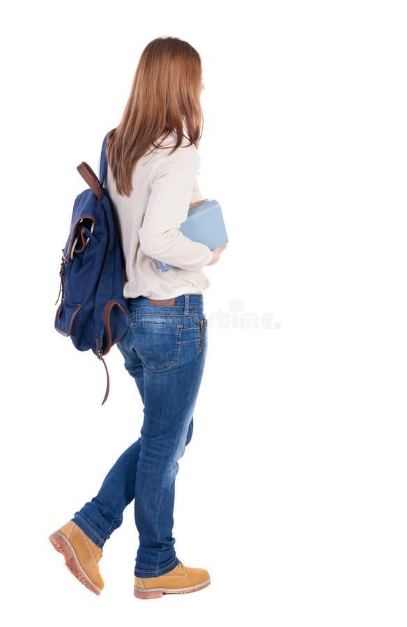 Mädchen mit einem Rucksack auf seinem zurück ist ein Stapel Bücher lizenzfreie stockfotografie