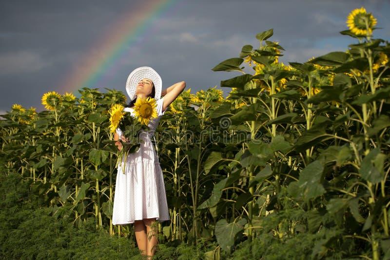 Mädchen mit einer Blumenstraußstellung auf dem Feld stockfotos