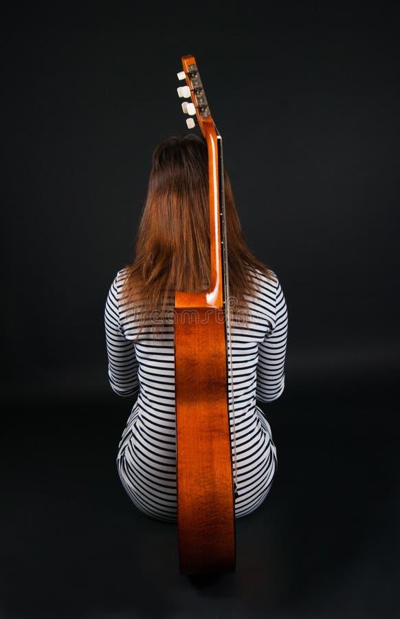 Mädchen mit einer Gitarre auf einem schwarzen Hintergrund lizenzfreie stockfotografie