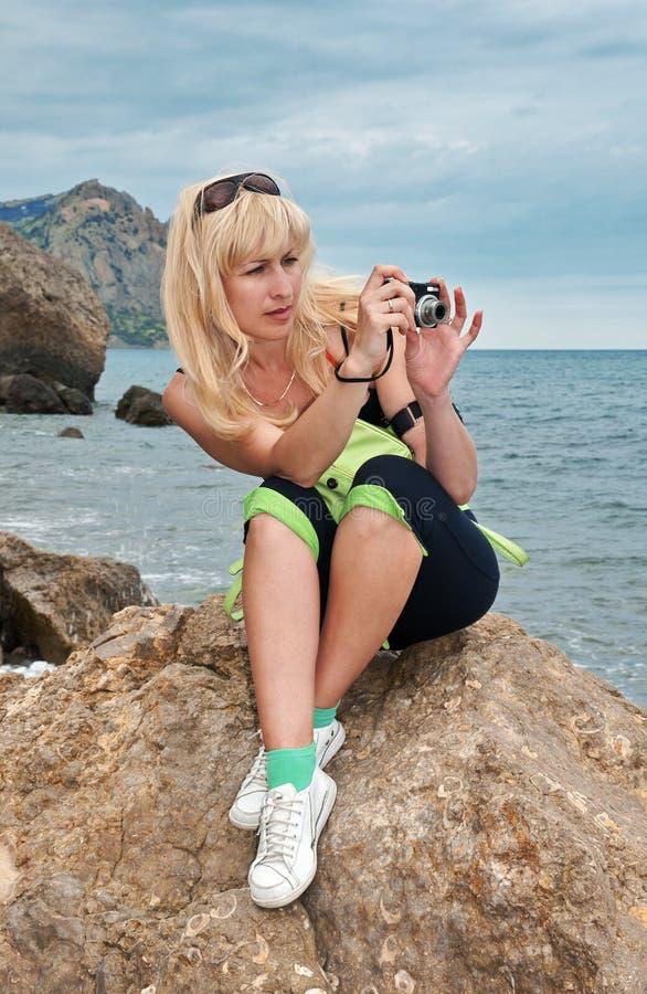 Mädchen mit einer Kamera auf Seeküste stockbild