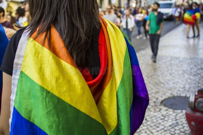 Mädchen mit einer Regenbogenflagge die lgbt Stolzparade aufpassend stockfoto