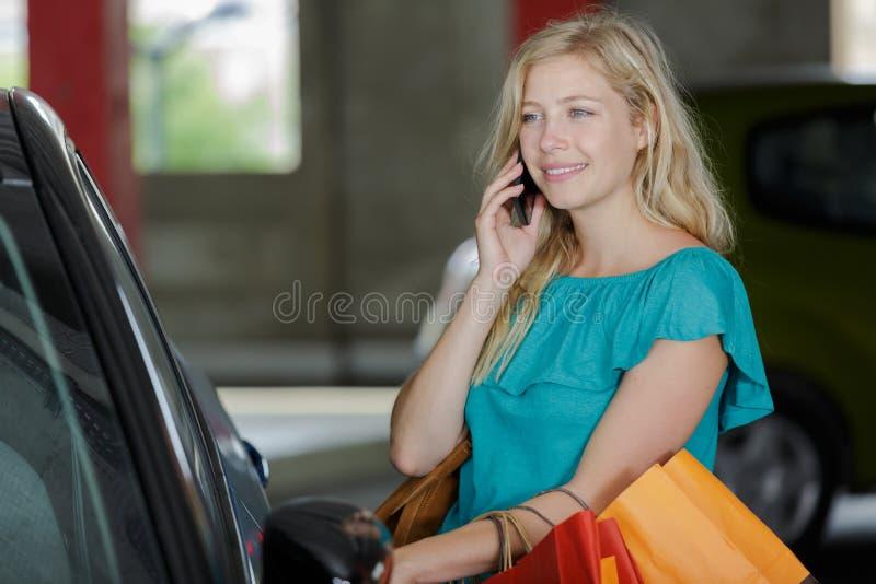Mädchen mit Einkaufstüten im Auto mit Handy lizenzfreie stockbilder