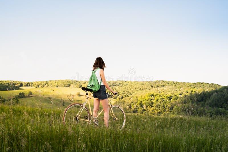 Mädchen mit Fahrrad schöne ländliche Landschaft genießend Junges pret stockfotos