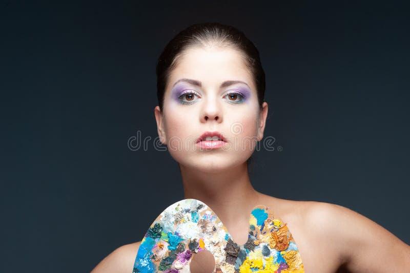 Mädchen mit Fantasiemake-up hält eine Palette stockfotografie