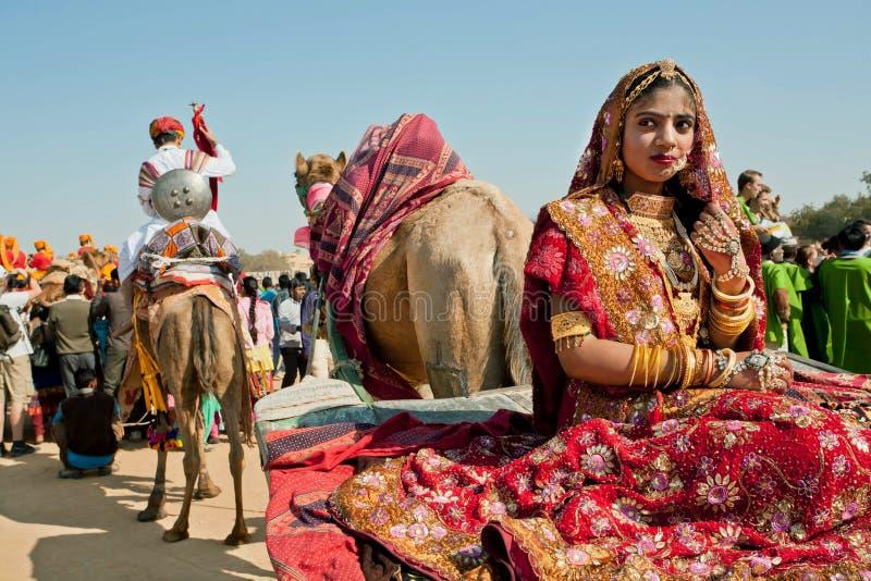Mädchen mit Goldschmuck sitzt im Kamelwarenkorb des Wüsten-Festivals stockbilder