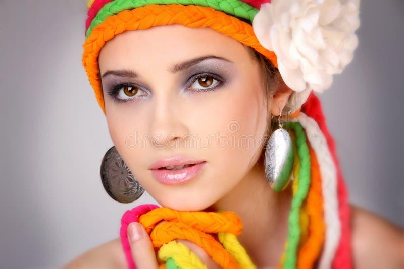 Mädchen mit großen Ohrringen und farbigen Flechten lizenzfreies stockbild