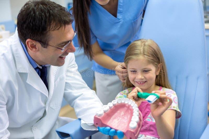 Mädchen mit großer Zahnbürste lernen vom Zahnarzt, wie man Zähne putzt stockbild