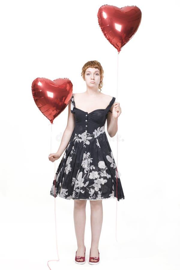 Mädchen mit heart-shaped Ballonen stockfoto