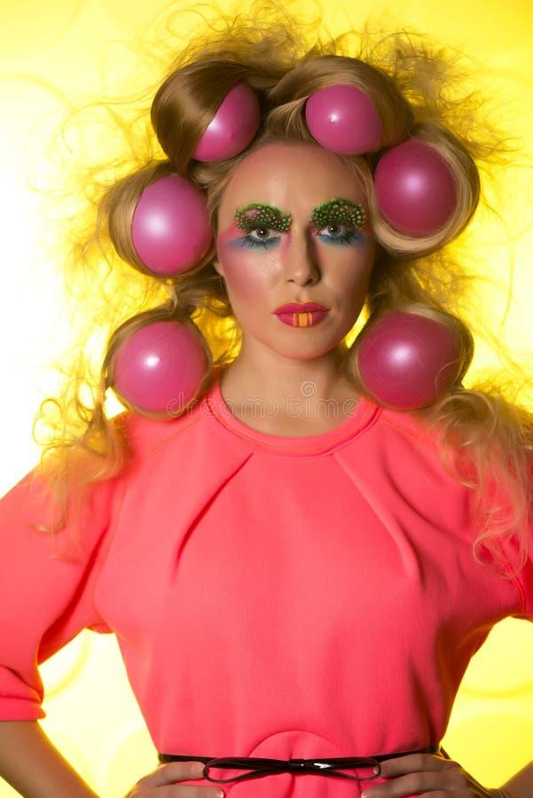 Mädchen mit hellen Make-up und Haarbällen auf gelbem Hintergrund stockbild