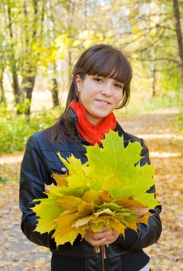 Mädchen mit Herbstblumenstrauß im Park lizenzfreie stockbilder