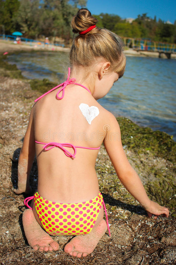 Mädchen mit Herz-förmiger Sonnencreme auf der Rückseite stockbild