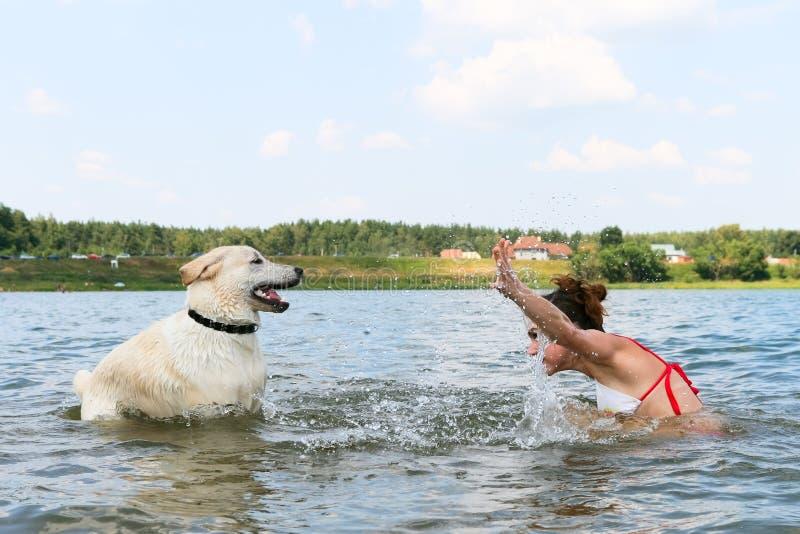 Mädchen mit Hund im Wasser lizenzfreie stockbilder